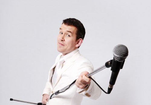 ian jones wearing white suit holding a microphone stand